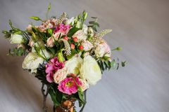 Wedding bouquet of white, red and pink flowers in a vintage vase. Stands on a light background. White and pink roses. Morning bride, copyspace Royalty Free Stock Photography