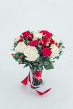 Wedding bouquet of white and red roses in fresh snow Royalty Free Stock Images