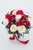 Wedding bouquet of white and red roses in fresh snow Royalty Free Stock Photography