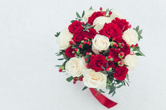 Wedding bouquet of white and red roses in fresh snow with copy space Stock Photo