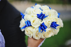 Wedding bouquet  with white rose and blue. Ribbon at hand of bride Stock Photography