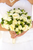 Wedding bouquet of white rose in hands of bride Stock Images
