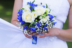 Wedding bouquet of white roses and blue ribbon. In the hands of the bride Royalty Free Stock Images