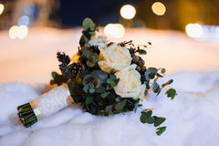 Wedding bouquet of white roses and cones in the snow Stock Photo