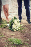 Wedding bouquet of white roses in the foreground. Wedding bouquet of white roses in the foreground against a background of a boy and girl legs Royalty Free Stock Photo