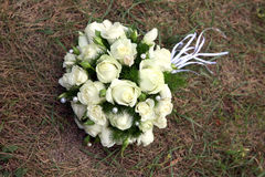 Wedding bouquet of white roses lying on the grass Royalty Free Stock Images