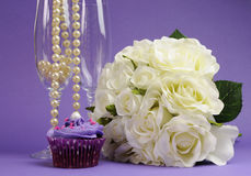 Wedding bouquet of white roses with purple cupcake and pearls in champagne glass Royalty Free Stock Photos