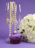 Wedding bouquet of white roses with purple cupcake and pearls in champagne glass - vertical. Royalty Free Stock Photos