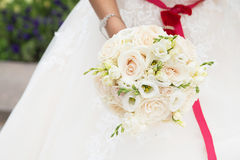 Wedding bouquet with white roses and red ribbon in hand Royalty Free Stock Image