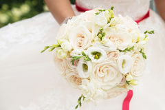Wedding bouquet with white roses and red ribbon in hand Royalty Free Stock Photography