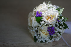 Wedding bouquet of white roses with wedding rings. On the table Royalty Free Stock Image