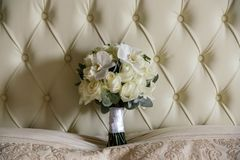 A wedding bouquet of white roses and white orchids stands at the head of the bed. Close up Royalty Free Stock Image