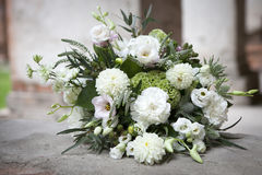The wedding bouquet in white tones of lisianthus, roses, dahlias and eucalyptus lying on stone ancient pavement. Wedding bouquet in white tones of lisianthus Stock Photography