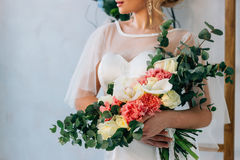 Wedding bouquet in white wedding dress in the hands of the beautiful bride. Wedding bouquet in white wedding dress stock photo