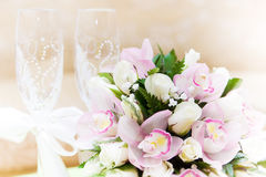 Wedding bouquet and wine glasses in the background Stock Images
