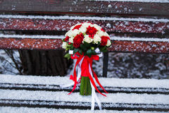 Wedding bouquet on a winter park bench Stock Images