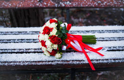 Wedding bouquet on a winter park bench Royalty Free Stock Image