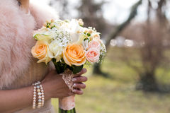 Wedding bouquet. A woman wearing a dress with fur, holding a bouquet of white and yellow flowers Royalty Free Stock Photo