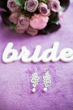 Wedding bouquet with word bride and earrings Stock Photos