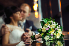 Wedding bouquet of yellow roses, purple flowers with bride and groom blurred in restaurant background Royalty Free Stock Image