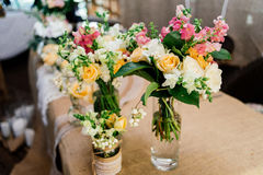 Wedding bouquets in vases. Wedding bouquets of yellow, white and pink roses are in vases on dinner table Royalty Free Stock Photo
