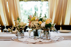 Wedding bouquets of yellow, white and pink roses are in vases. On dinner table Royalty Free Stock Image