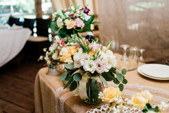 Wedding bouquets of yellow, white and pink roses are in vases. On dinner table Royalty Free Stock Photography
