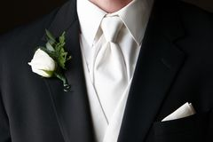 Wedding Boutonniere. Pinned on the collar of a black wedding suit with white tie and handkerchief in pocket Stock Photography