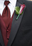 Wedding Boutonniere. Red calla lily boutonniere on wedding suit jacket of groom royalty free stock images