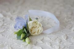 Wedding boutonniere flower. Roses and blue delphinium white ribbon close up Stock Images