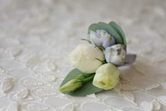 Wedding boutonniere flower. Roses and blue delphinium white ribbon close up Stock Photos