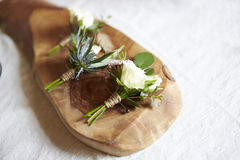 Wedding boutonniere on wood. A set of flower wedding boutonniere on a slab of wood. White linen background behind wood Royalty Free Stock Images