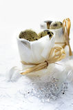 Wedding Breakfast. Concept image for a wedding breakfast. Quails eggs in paper packets tied with raffia on white lace with semi-precious stones and feathers Stock Image