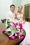 Wedding. Bridal bouquet on background of happy newlyweds Royalty Free Stock Photos