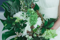 Wedding bridal bouquet with big tropical green leaves and white flowers.  Royalty Free Stock Photo