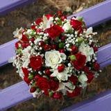 Wedding bridal bouquet lying on  park bench. Royalty Free Stock Photo