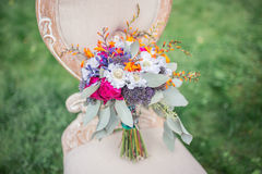 Wedding bridal bouquet with purple, blue and orange flowers Royalty Free Stock Photo