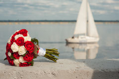 Wedding bridal bouquet with res and white roses against the background of theyacht. Wedding concept stock photo