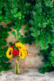 Wedding bridal bouquet of sunflowers in on a stone bench and han. Ging on the background of green leaves. Wedding in Montenegro, Perast royalty free stock photo