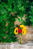 Wedding bridal bouquet of sunflowers in on a stone bench and han. Ging on the background of green leaves. Wedding in Montenegro, Perast royalty free stock images
