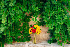 Wedding bridal bouquet of sunflowers in on a stone bench and han. Ging on the background of green leaves. Wedding in Montenegro, Perast stock photography