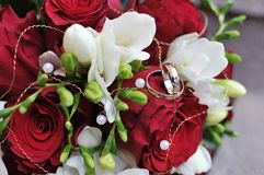 Wedding bridal bouquet and two golden rings Stock Image