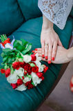 Wedding Bridal bouquet with white and red roses in her hands on blue background. Red nails Stock Photos