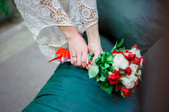 Wedding Bridal bouquet with white and red roses in her hands on blue background. Red nails Royalty Free Stock Images