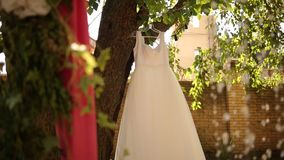 Wedding bridal dress hanging on a tree at rustic style wedding. Country decor with pink flower bouquets, garlands and stock video
