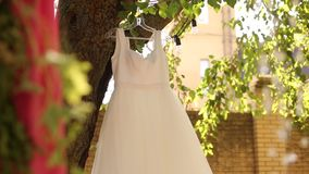 Wedding bridal dress hanging on a tree at rustic style wedding. Country decor with pink flower bouquets, garlands and stock footage