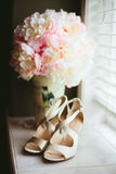 Wedding Bridal Shoes with Peony Bouquet. Wedding shoes with a peony bouquet on a window sill the morning of a wedding day Royalty Free Stock Images