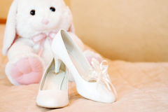 Wedding bridal shoes and plush toy bunny. White Stock Images