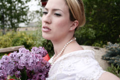 Wedding Bride 1. Bride looks off into the distance while holding her boquet of Lilacs royalty free stock images