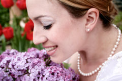 Wedding Bride 2. Blushing bride smiles as she smells her lilac wedding boquet Royalty Free Stock Image